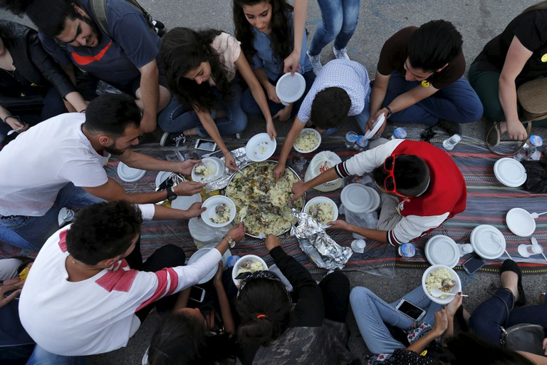 """People eat their Iftar (breaking of fast) during a local initiative called """"Let's Have Iftar Together"""" during the holy fasting month of Ramadan in Amman, Jordan June 27, 2015. © Muhammad Hamed, Reuters"""
