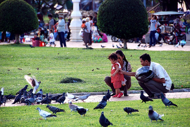 A family feeds the birds that gather at the gardens in front of the Silver Pagoda