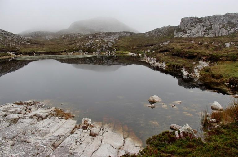 Peaty lochan on Tully Mountain | © Alan Reid/Geograph