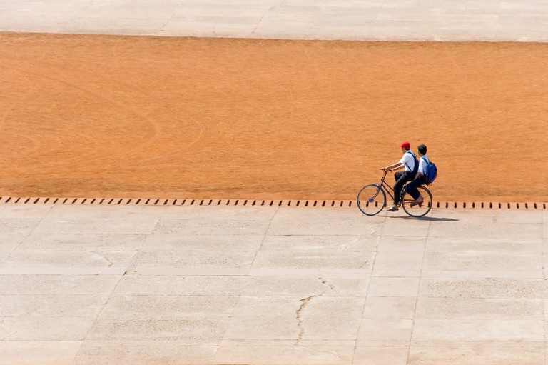 Boys cycle through the stadium in Phnom Penh