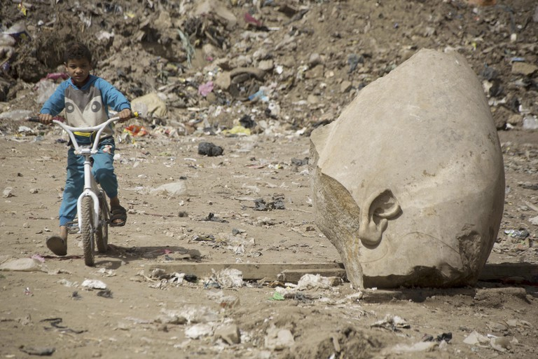 A young boy cycles past the fragment of a statue