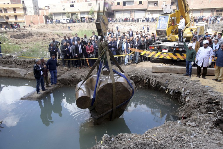 The statue in the process of being lifted out of the groundwater