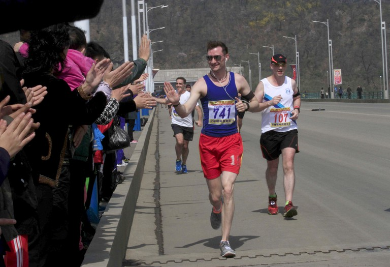 Runners high five spectators during the 2017 Pyongyang Marathon