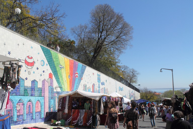Passersby enjoy looking at the mural while walking through the Feira da Ladra