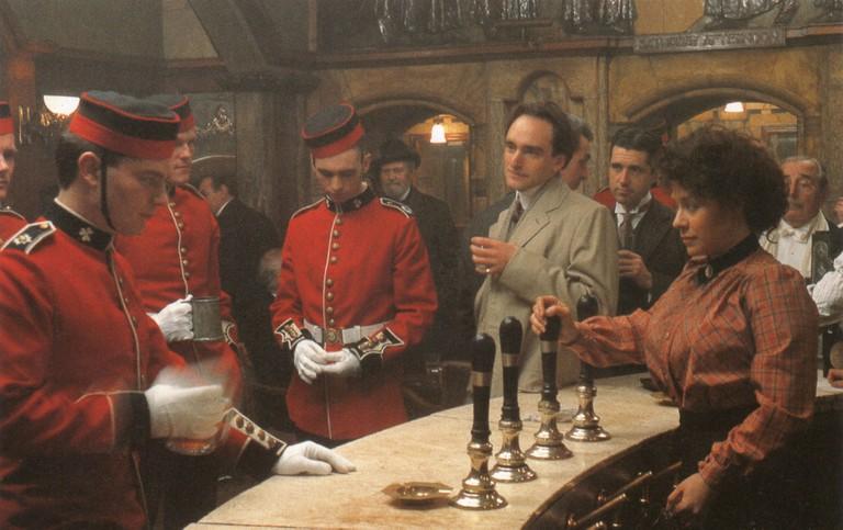 Mary Tandy as Viscount Risley (in raincoat)