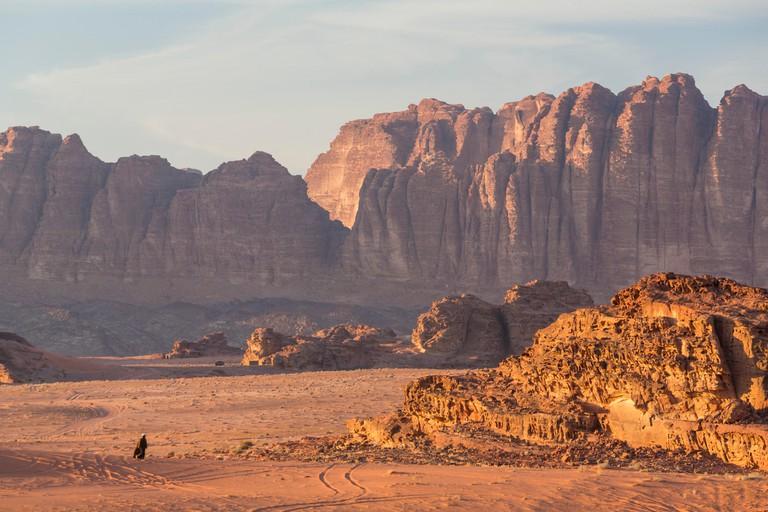 Man walking across desert, Wadi Rum, Jordan.