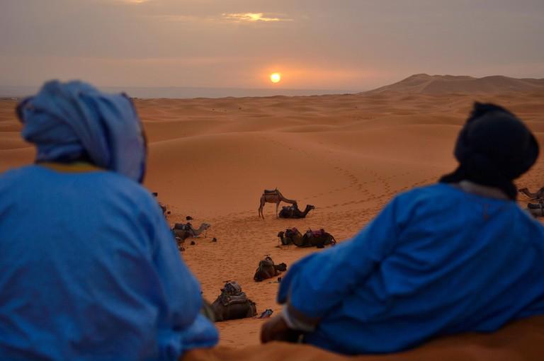 Berber men watching sunrise, Erg Chebbi, Sahara Desert, Merzouga, Morocco