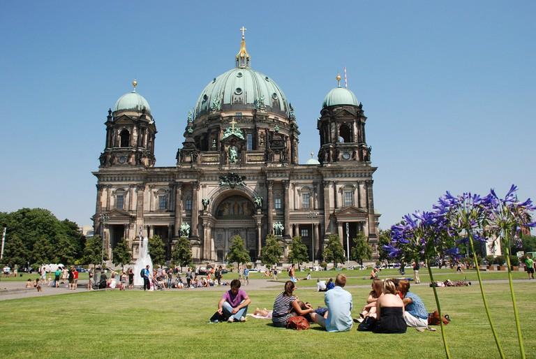 Enjoying the sunshine, green grass and flowers outside Berlin's famous Nikolairkirche church