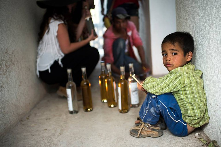 Little boy watches as the mezcal is bottled | © Cantimplora Travel