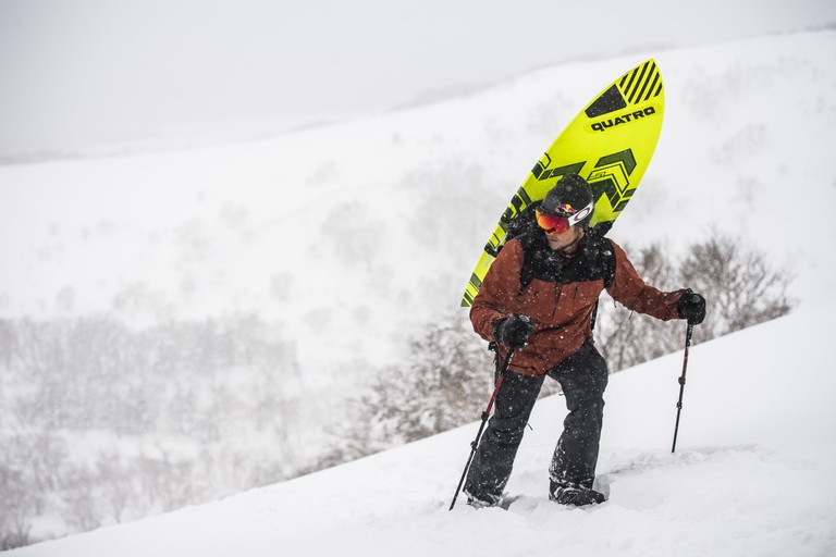 Siver hikes Rishiri Mountain with his board strapped to his back.