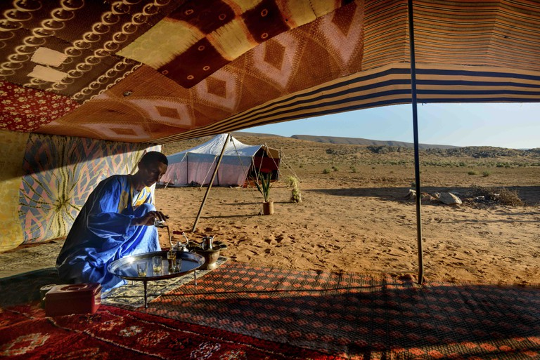 Berber man preparing tea for guests at a camp near Guelmim in the Sahara desert, Morocco.