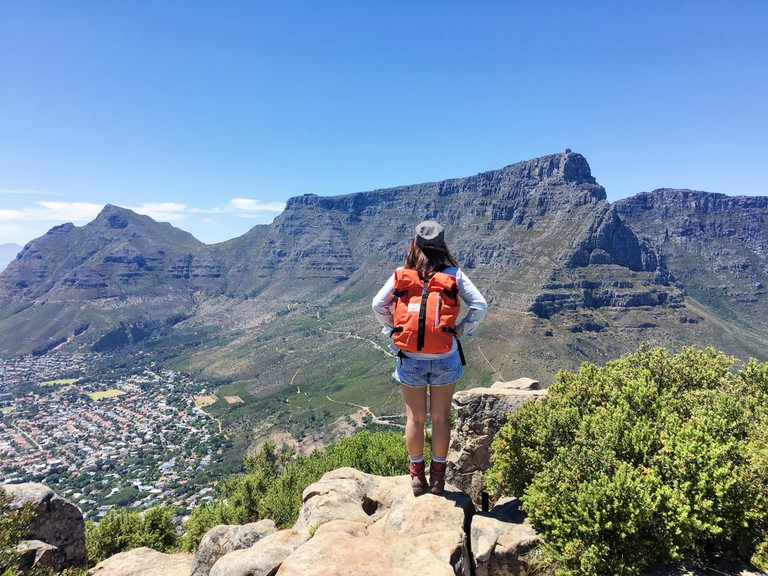 A hiker checks out Table Mountain from Lion's Head