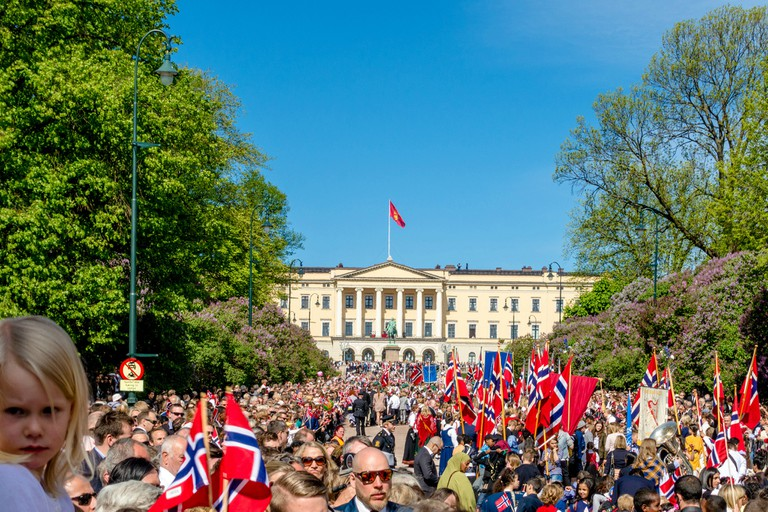 Happy Norwegians wave at the Royal Family at the Castle in Oslo