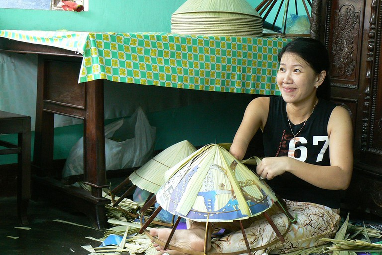 A Hue woman with just one arm is making conical hats