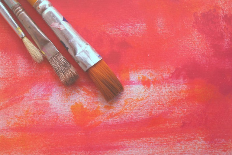 Paintbrushes against a red painting I