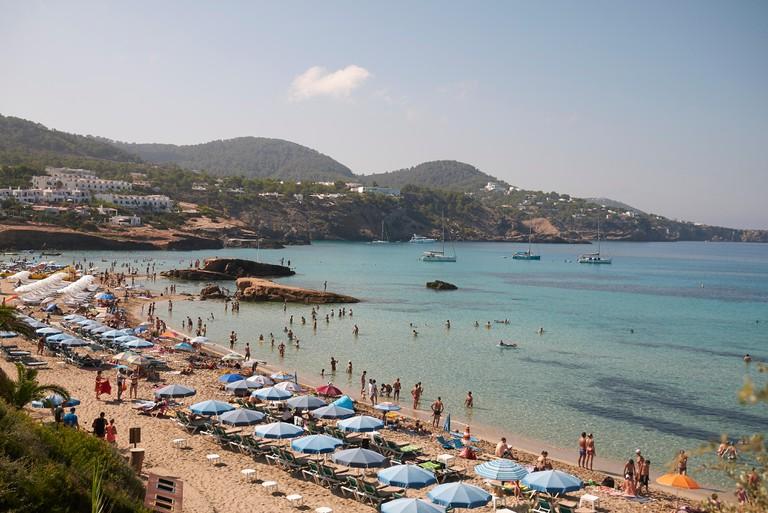 People enjoy the beach in Ibiza, Spain