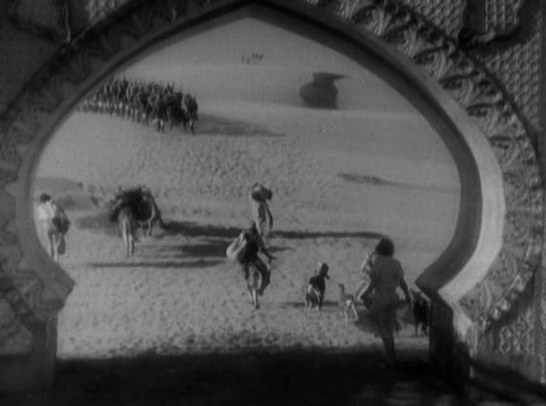 """Amy Jolly (Marlene Dietrich) passes beneath an arabesque arch as she follows her legionnaire lover (Gary Cooper) at the end of """"Morocco"""" (1930)"""