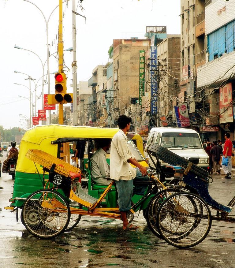 An auto-rickshaw and a cycle-rickshaw wait at a signal in Delhi