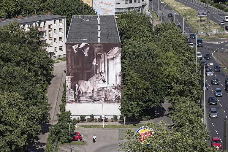 The mural looks onto the parking lot and Drive-Thru of a Burger King | © Nika Kramer / Urban Nation Berlin