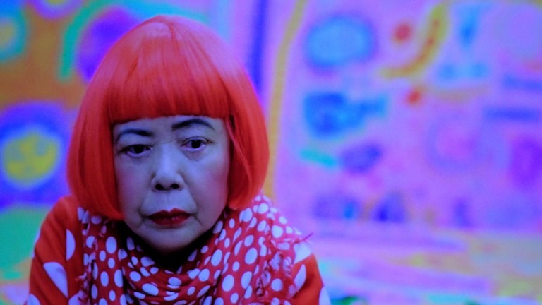 Yayoi Kusama is easily recognizable with her trademark red wig