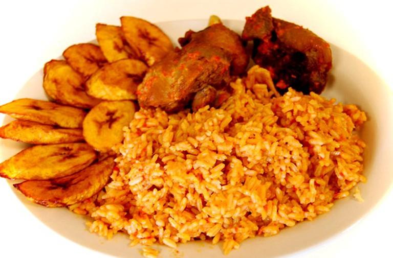 Nigerian jollof rice with fish and fried plantain