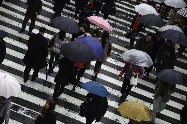 Crossing the street with umbrellas in Osaka