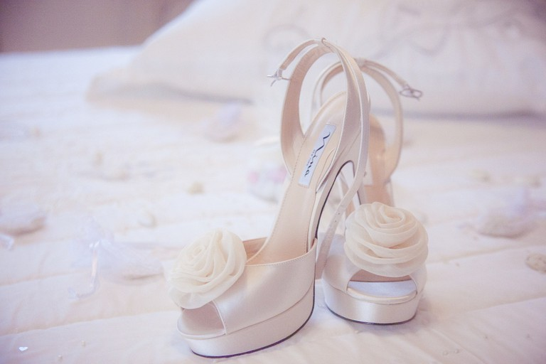 The bride writes the names of her single bridesmaids on the sole of her shoes