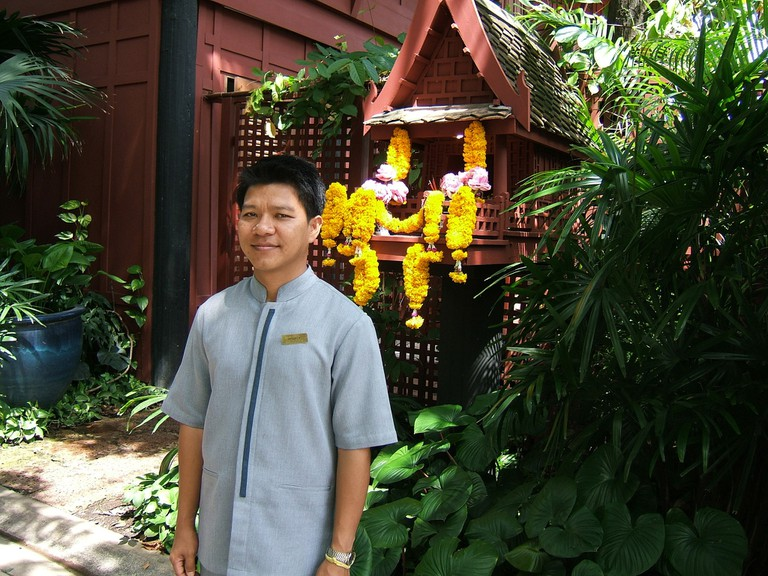 A man poses in front of a spirit house