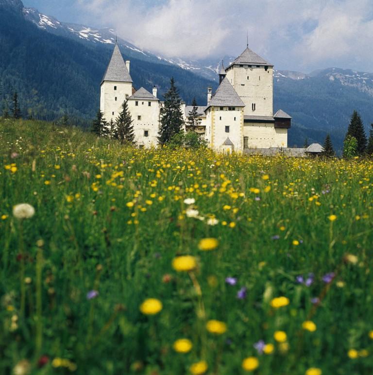 A castle across a meadow in Austria