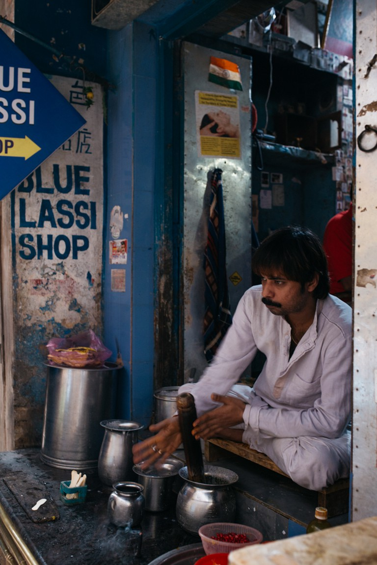 A man preparing bhang thandai in a shop in Varanasi