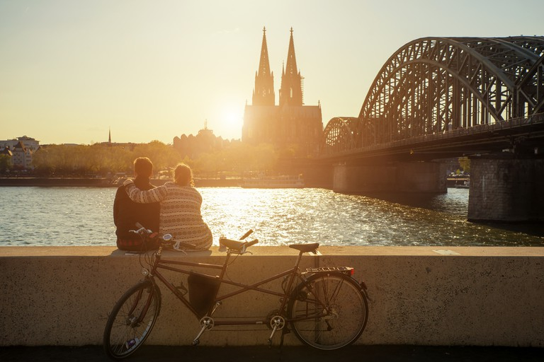 A young couple watches the sun set over Cologne Cathedral