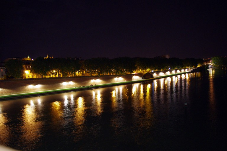 The city lights reflecting on the Garonne River at night