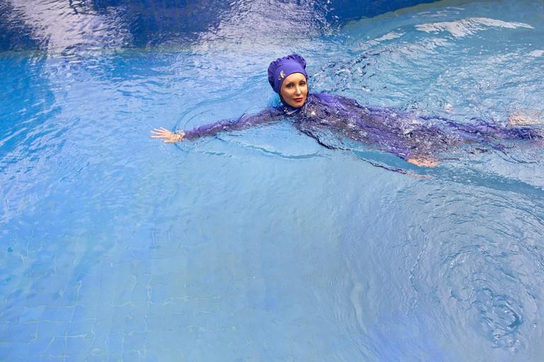 Woman wearing a burkini swimming/ Shutterstock images