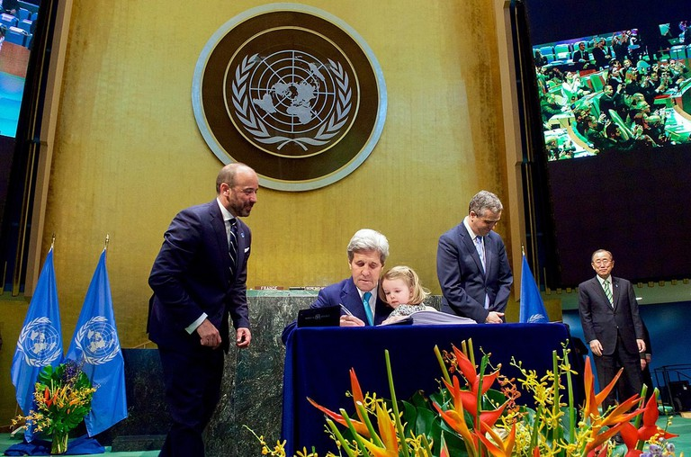 John Kerry signing the COP 21 with his granddaughter and UN Secretary General Ban Ki-Moon in 2016