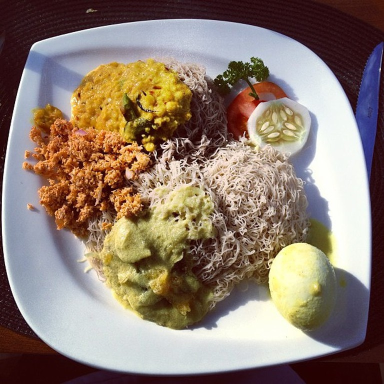 A served plate of Sri Lankan String Hopper breakfast with potato curry, pol sambol, dahl curry and a boiled egg.