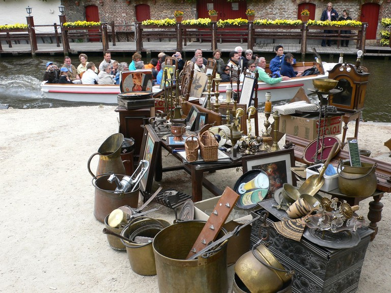A brocante stand at the Dijver with a signature Bruges tourist boat in the background   © Dez & Jude / Flickr