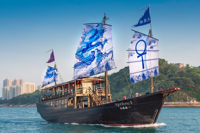 The ornate blue and qhite sails of Aqua Luna II are adorned with Chinese imperial-style dragons. Caption