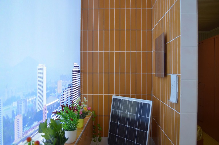 Potted plants and solar panels are typical items found on Pyongyang balconies