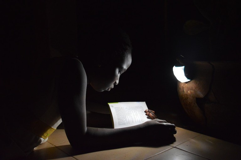 "A child in Senegal uses the ""Little Sun Diamond"" to read in the dark 