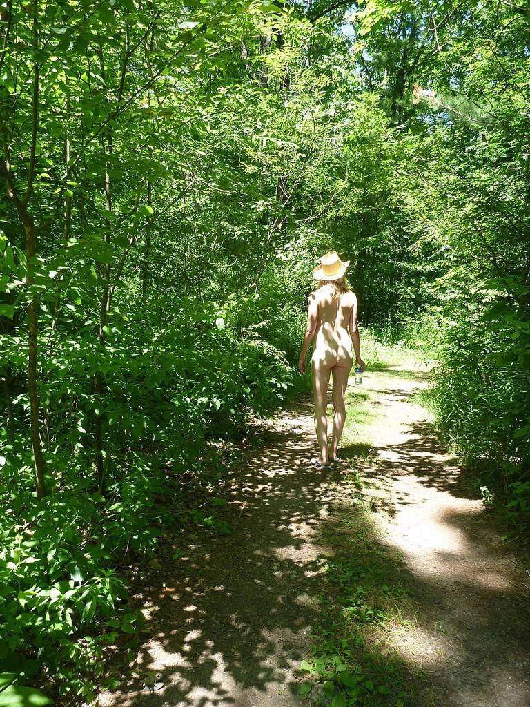Nudist woman walking in forest