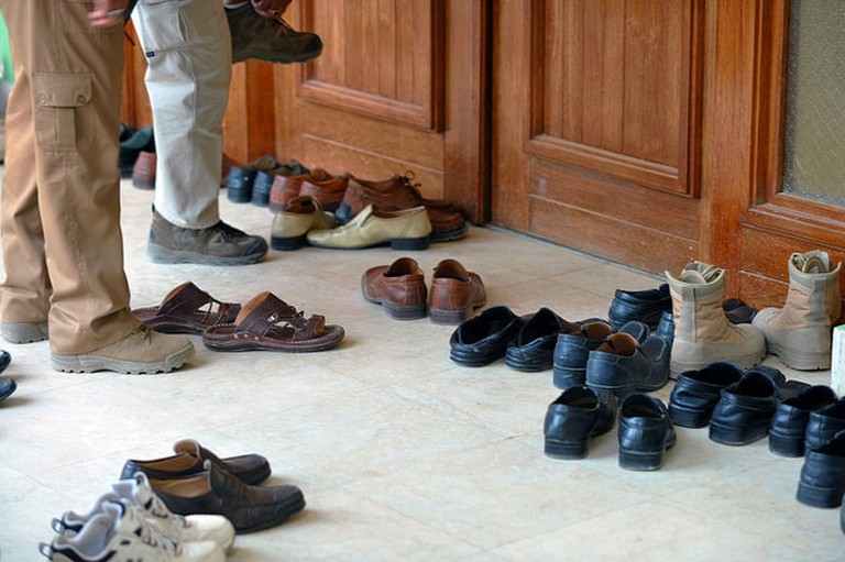 Men removing shoes before entering a house