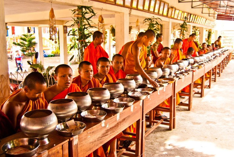 "Buddhist monks are in expectation of food and money offerings in Pchum Ben (""Ancestors' Day""), Wat Krom, Sihanoukville, Cambodia"