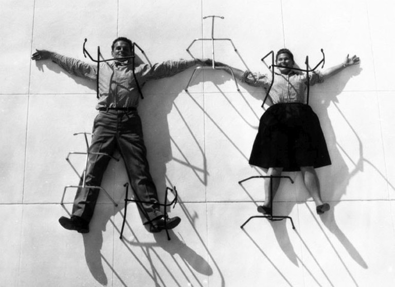 04. An Eames Celebration. Charles and Ray Eames posing with chair bases ∏ Eames Office LLC