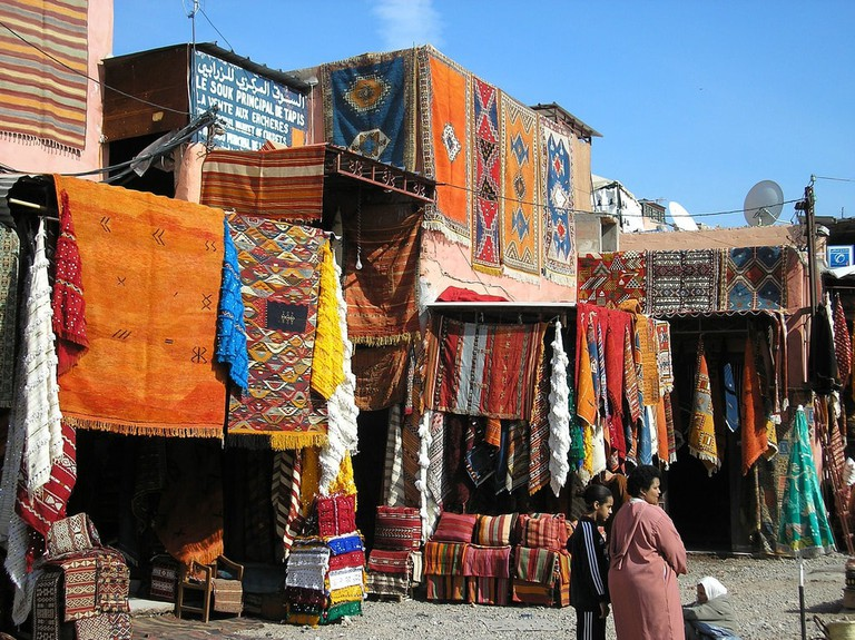Colourful rugs hanging from the walls in the medina of Marrakech