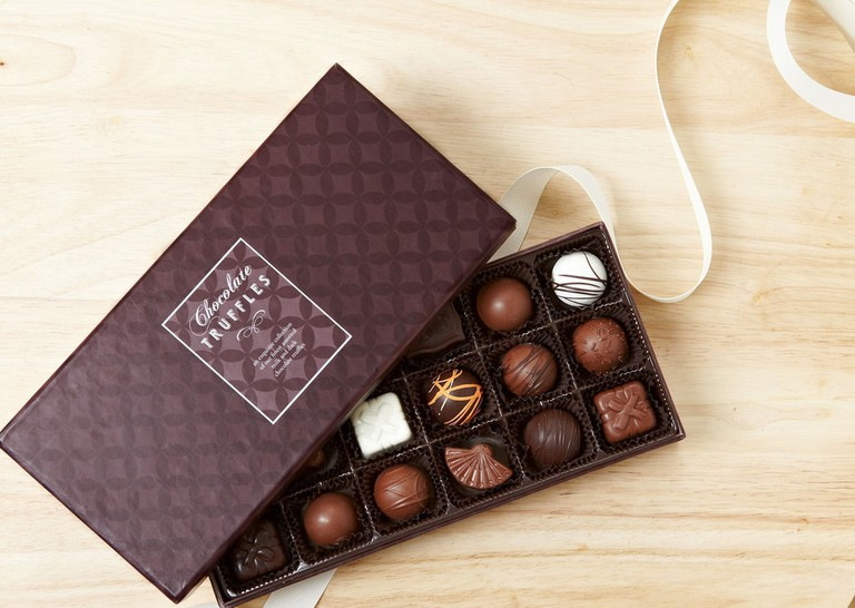 Assorted chocolate truffles in box with white ribbon on wood table