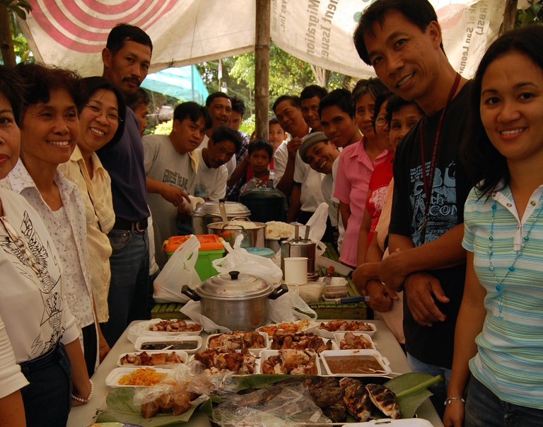 Filipinos surrounding table of food