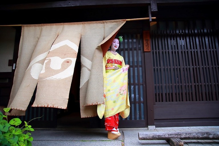 A maiko stands outside Hosoo, the Kyoto textiles company