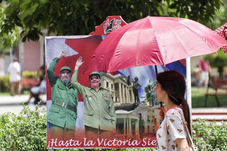 A woman walks past a poster showing the Castro brothers in Cuba