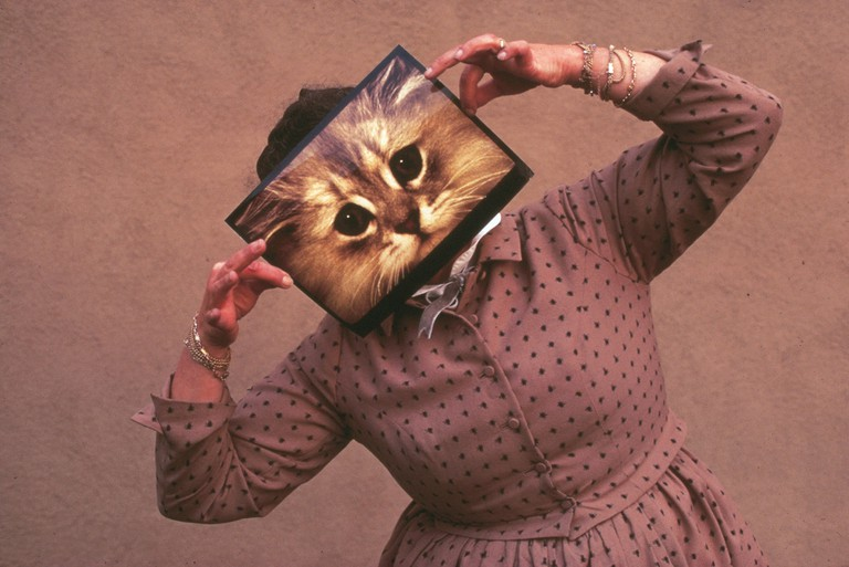 Ray Eames posing with cat photograph, 1970