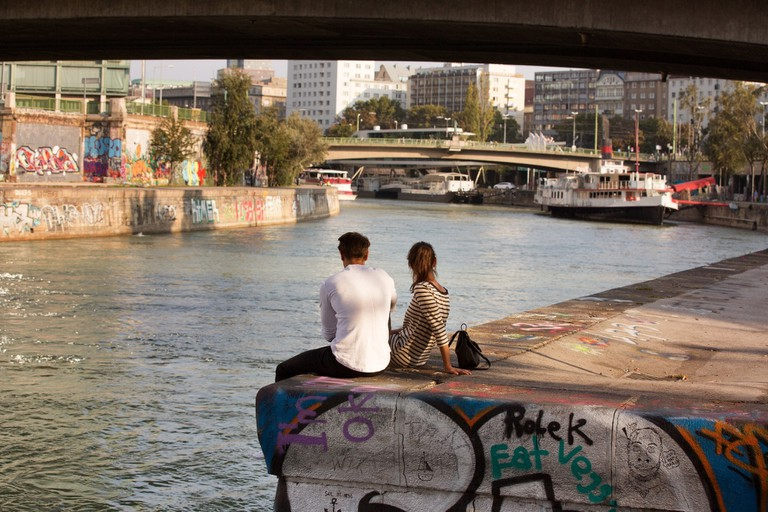 A couple sit by the Danube Canal